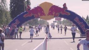 En la avenida, la carretera de asfalto corre en dos direcciones, separadas cercando los corredores de marat?n, en pintura del hol almacen de metraje de vídeo