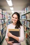 En la biblioteca - estudiante bonito con los libros que trabajan en un h Imagen de archivo