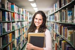 En la biblioteca - estudiante bonito con los libros que trabajan en un h Fotografía de archivo libre de regalías