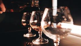 En la cámara lenta el proceso de llenar un vidrio de whisky de la botella Primer agradable Alimento almacen de video