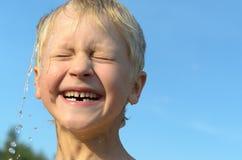 En la cabeza de un muchacho luz-cabelludo vierte una corriente del agua contra el cielo azul y él disfruta Fotografía de archivo