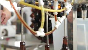 En la cervecería, la máquina substituye las botellas debajo de la boca para llenarlas de la cerveza almacen de video
