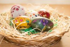 En la cesta de mimbre son los huevos de Pascua coloridos Fotos de archivo libres de regalías