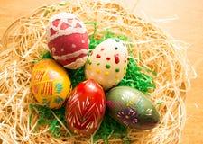 En la cesta de mimbre son los huevos de Pascua coloridos Imagen de archivo libre de regalías