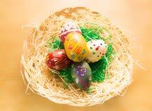 En la cesta de mimbre son los huevos de Pascua coloridos Imagenes de archivo