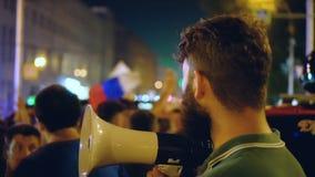En la ciudad de la noche un hombre con un altavoz mira a la muchedumbre de manifestantes almacen de metraje de vídeo