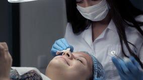 En la clínica, el cosmetologist hace al cliente un limpiamiento facial mecánico almacen de metraje de vídeo