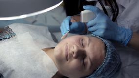 En la clínica, el cosmetologist hace al cliente un limpiamiento facial mecánico metrajes