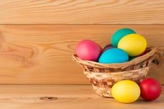 En la composición de Pascua de los tableros de madera con los huevos coloreados Imágenes de archivo libres de regalías