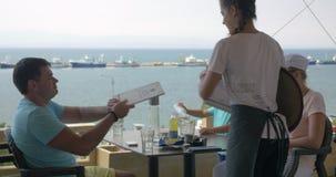 En la costa de mar de la ciudad Perea, Grecia que una familia joven se sienta en café almacen de video