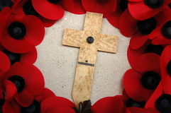 En la cruz de la conmemoración rodeada por Poppies Foto de archivo libre de regalías