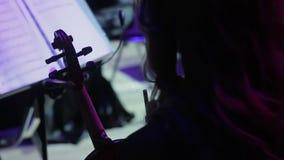 En la etapa del teatro, un violinista de la mujer de una orquesta sinfónica sostiene los violines en sus manos antes del funciona metrajes