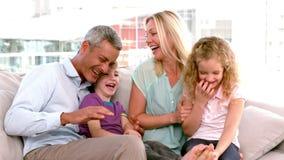 En la familia feliz de la cámara lenta que se sienta en el sofá almacen de video