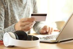 En la línea música de compra del comprador con un ordenador portátil Imágenes de archivo libres de regalías