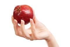 En la mano de las mujeres una manzana roja Fotos de archivo