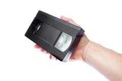 En la mano de un viejo formato VHS de la videocinta del hombre. Imagen de archivo libre de regalías