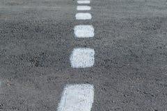 En la marca del pavimento Línea blanca intermitente áspera Foto de archivo