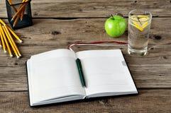 En la mesa, abra el diario con las páginas en blanco y accessori de la oficina Imagenes de archivo