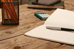 En la mesa, abra la libreta con la pluma y la calculadora Imagen de archivo