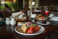 En la mesa de desayuno hay una placa con las frutas exóticas cortadas Imagen de archivo libre de regalías