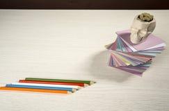 En la mesa etiquetas engomadas coloreadas dobladas para las notas Imagen de archivo