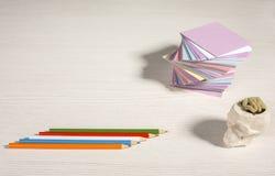 En la mesa etiquetas engomadas coloreadas dobladas para las notas Foto de archivo libre de regalías