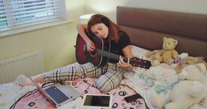 En la muchacha del adolescente del fin de semana pase el tiempo en su sitio que juega en una guitarra su tableta y el cuaderno es metrajes