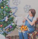 En la muchacha embarazada del Año Nuevo cerca del árbol de navidad Imagen de archivo