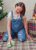 En la muchacha embarazada del Año Nuevo cerca del árbol de navidad Imágenes de archivo libres de regalías