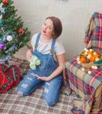 En la muchacha embarazada del Año Nuevo cerca del árbol de navidad Foto de archivo