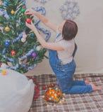 En la muchacha embarazada del Año Nuevo cerca del árbol de navidad Fotografía de archivo
