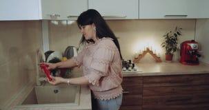 En la mujer de la cocina están lavando las legumbres en el fregadero 4K metrajes