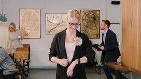 En la mujer de la oficina conceptora que usa su smartwatch que lleva en una mano Muchacha sonriente que trabaja con nueva tecnolo metrajes