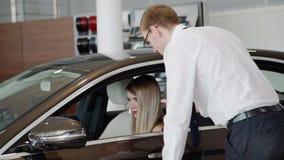 En la mujer de la sala de exposición que se sienta en un coche marrón, que el vendedor dice metrajes