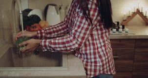 En la mujer del primer de la cocina se lavan las verduras 4K almacen de metraje de vídeo