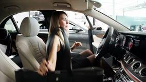 En la mujer joven de la sala de exposición a sentarse en el nuevo coche y para explorar el salón almacen de video