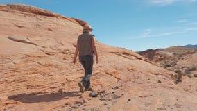 En la mujer que se divierte del movimiento que camina en el barranco rojo de la roca en desierto almacen de metraje de vídeo