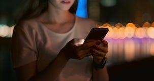 En la noche, una chica joven sostiene un smartphone en sus manos y miradas en la pantalla almacen de metraje de vídeo