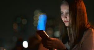 En la noche, una chica joven sostiene un smartphone en sus manos y miradas en la pantalla almacen de video