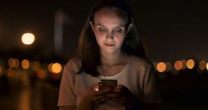 En la noche, una chica joven sostiene un smartphone en sus manos y miradas en la pantalla metrajes