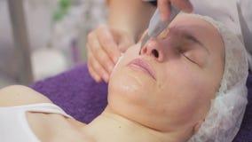 En la oficina de un cosmetologist, una mujer es 40 años en procedimientos Limpieza ultrasónica de la cara almacen de video