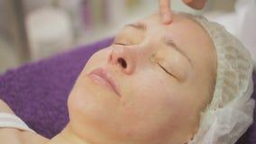 En la oficina de un cosmetologist, una mujer es 40 años en procedimientos Limpieza ultrasónica de la cara metrajes