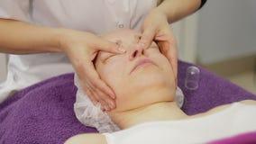 En la oficina de un cosmetologist, una mujer es 40 años en procedimientos Masaje de cara almacen de video