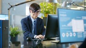 En la oficina el hombre de negocios agitado trabaja en una C personal de escritorio fotos de archivo libres de regalías