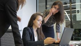 En la oficina tres las mujeres jovenes se divierten delante del ordenador portátil en la mesa almacen de metraje de vídeo