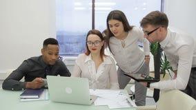 En la oficina un equipo internacional se está inspirando para un ordenador portátil almacen de video