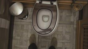 En la opinión acogedora del cuarto de baño desde arriba sobre el retrete Piernas de una situación del hombre delante del retre almacen de video