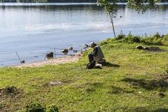 En la orilla del lago, un hombre está pescando con algunas cañas de pescar Imagen de archivo libre de regalías