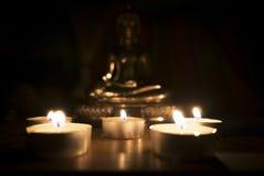 En la oscuridad de la luz de la vela con la estatua borrosa de Buda en el fondo Fotos de archivo