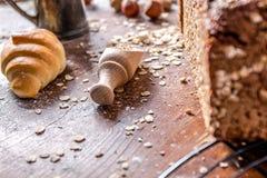 En la panadería, aún la vida con los mini cruasanes, el pan, la leche, las nueces y la harina Imagen de archivo